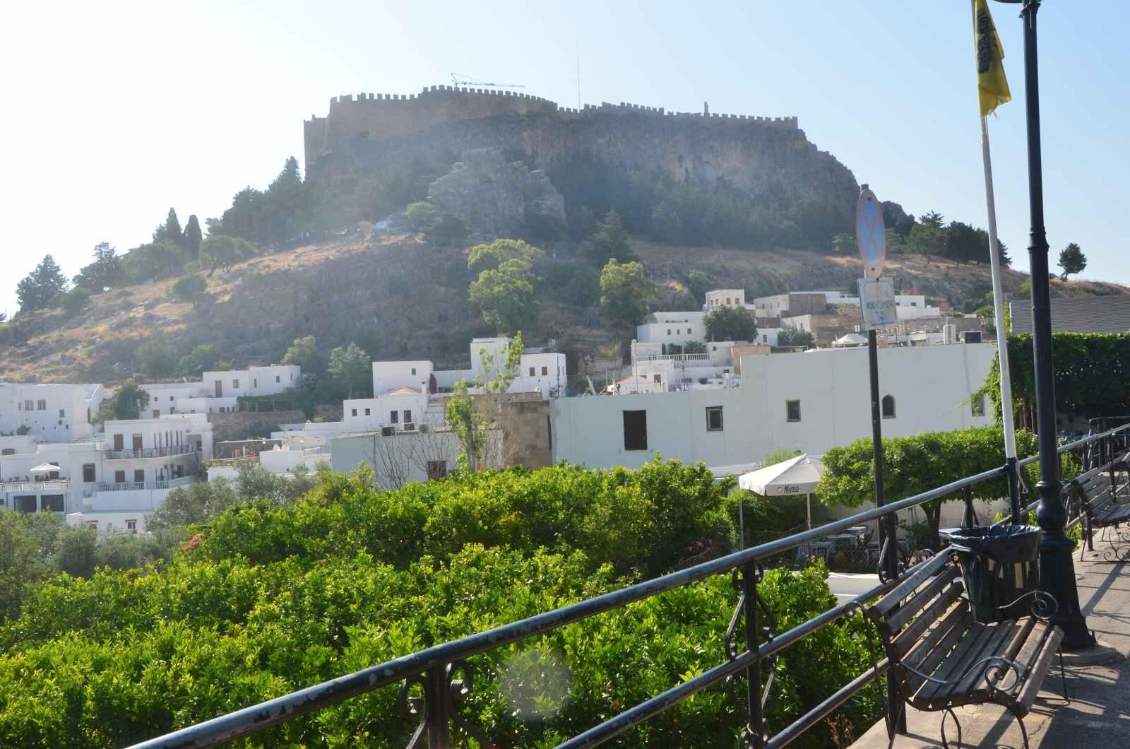 Foto 2: Ne úplně podařený záběr na kopec s akropolí nad městečkem Lindos – foceno z parkoviště, před vstupem do uliček městečka, doprava dolů je pak výhled na krásnou pláž – viz další fotka.